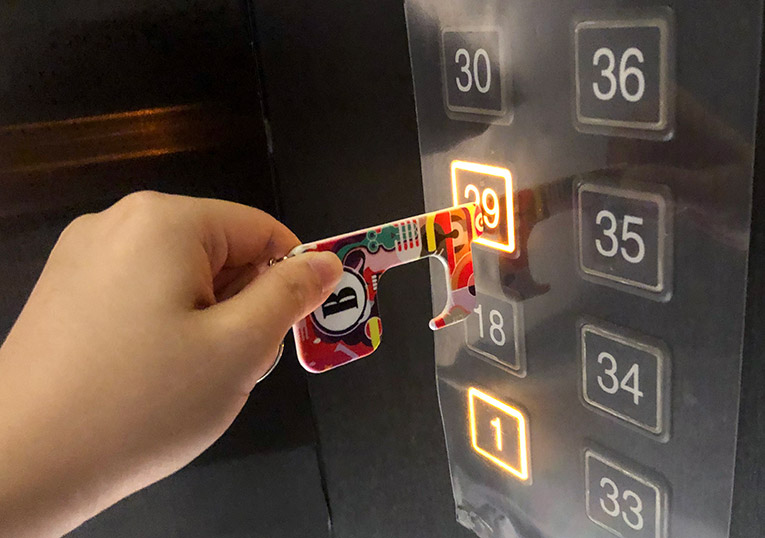 Pressing a lift button with a polymer germ free keyring